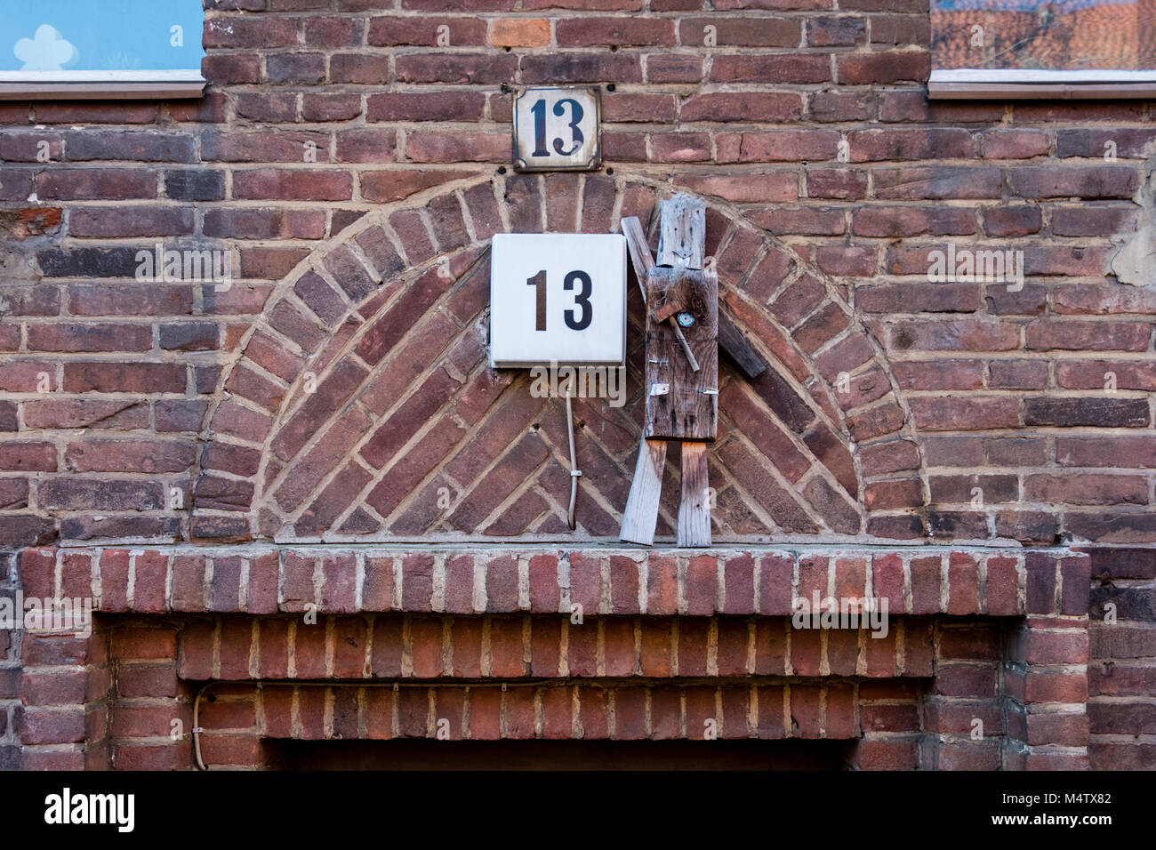 Berlin home. Building detail, Klinker brick wall with naive wooden sculpture of man on house number thirteen. - Stock Image
