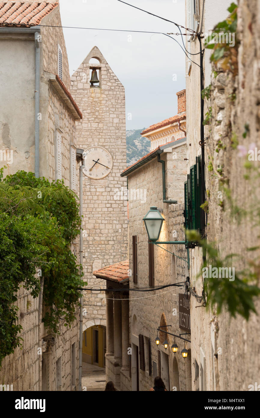 Narrow alleyway in Rab old town with clock / bell tower and houses built of white bricks and red roof tiles - Stock Image