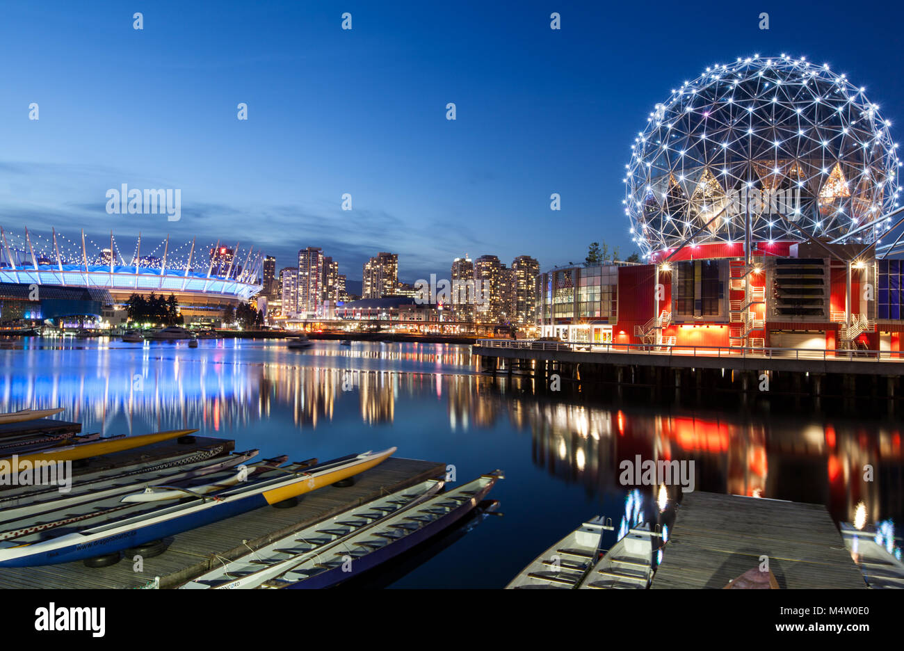 Science World and BC Place reflecting off the waters of False Creek, taken at sunrise with blue skies and a sense - Stock Image