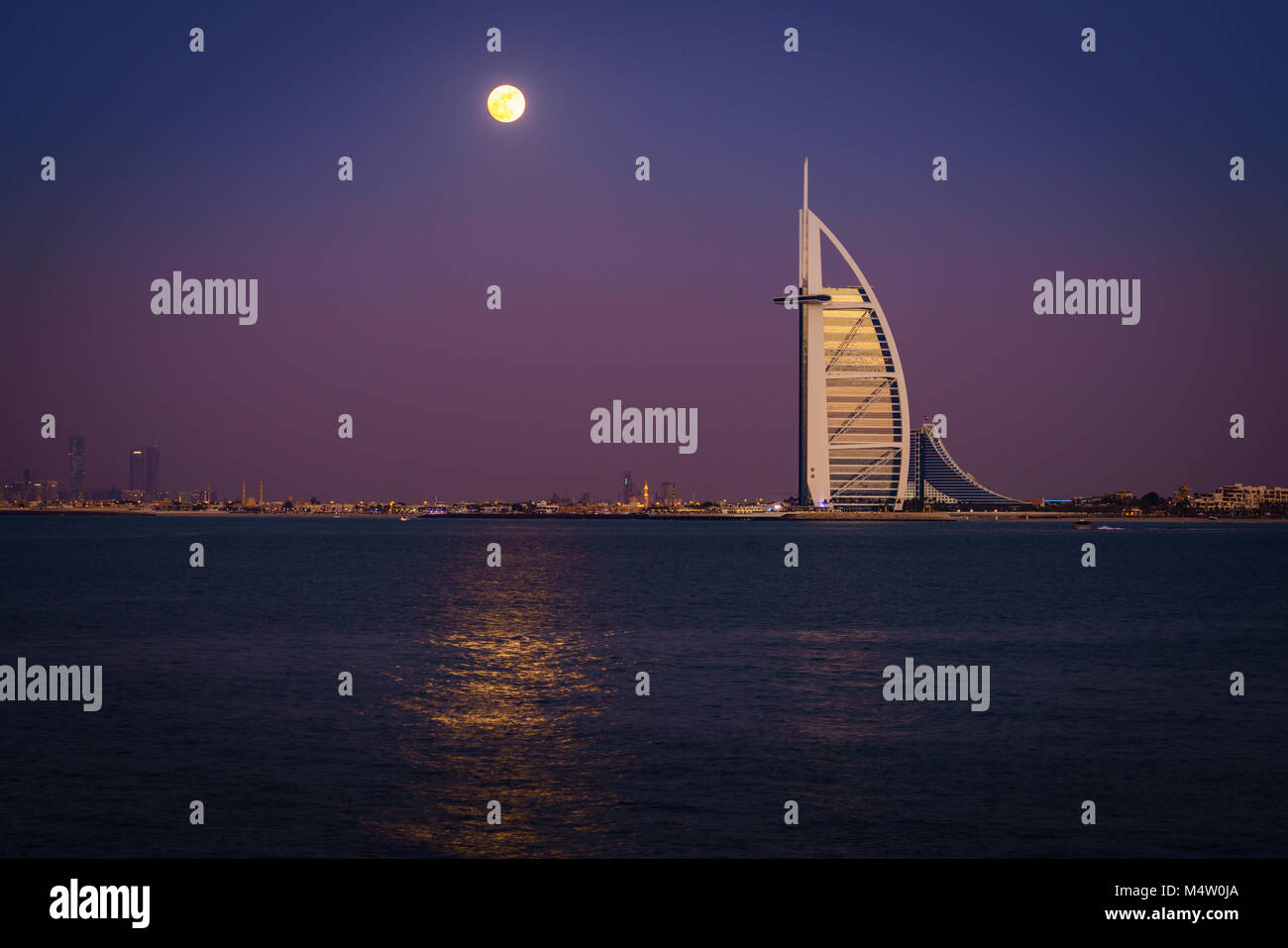 Dubai, UAE, December 13, 2016: full moon is rising over Burj Al Arab - the world's only 7-star luxury hotel - Stock Image