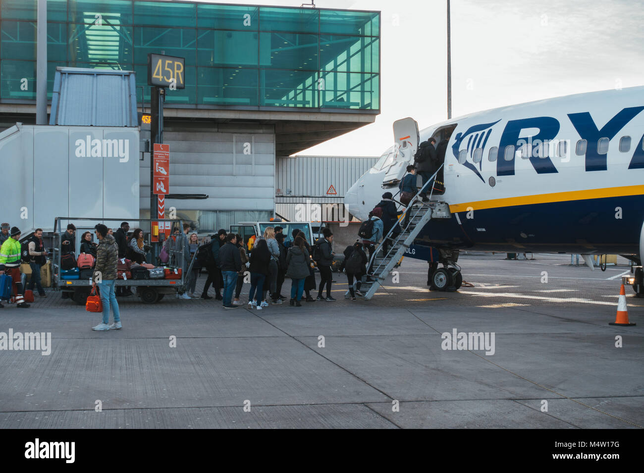 Passengers boarding a Ryanair jet after their new cabin bag policy came into effect - requiring them to forfeit - Stock Image