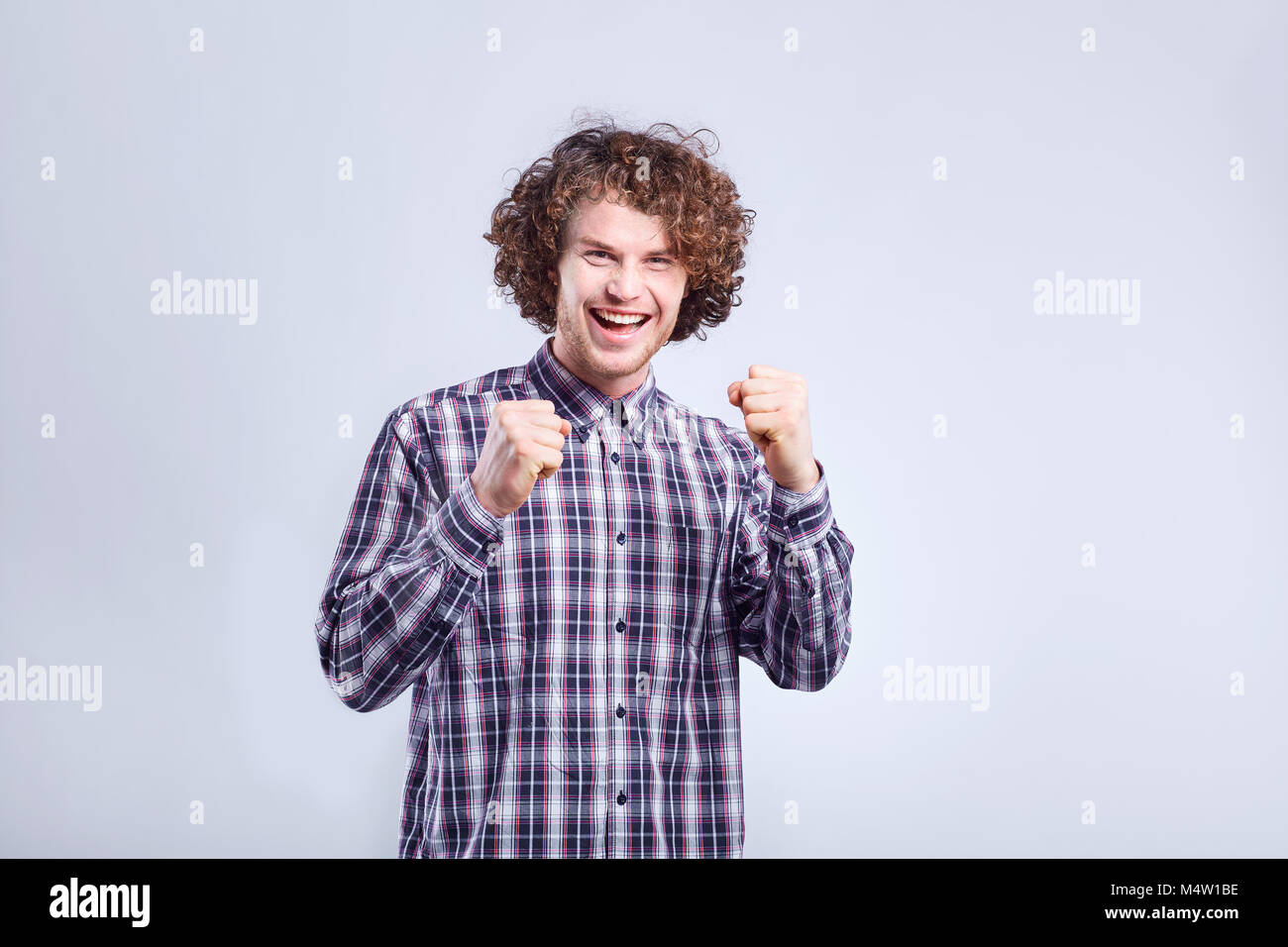 Curly young man surprised, joyful emotion on his face. - Stock Image