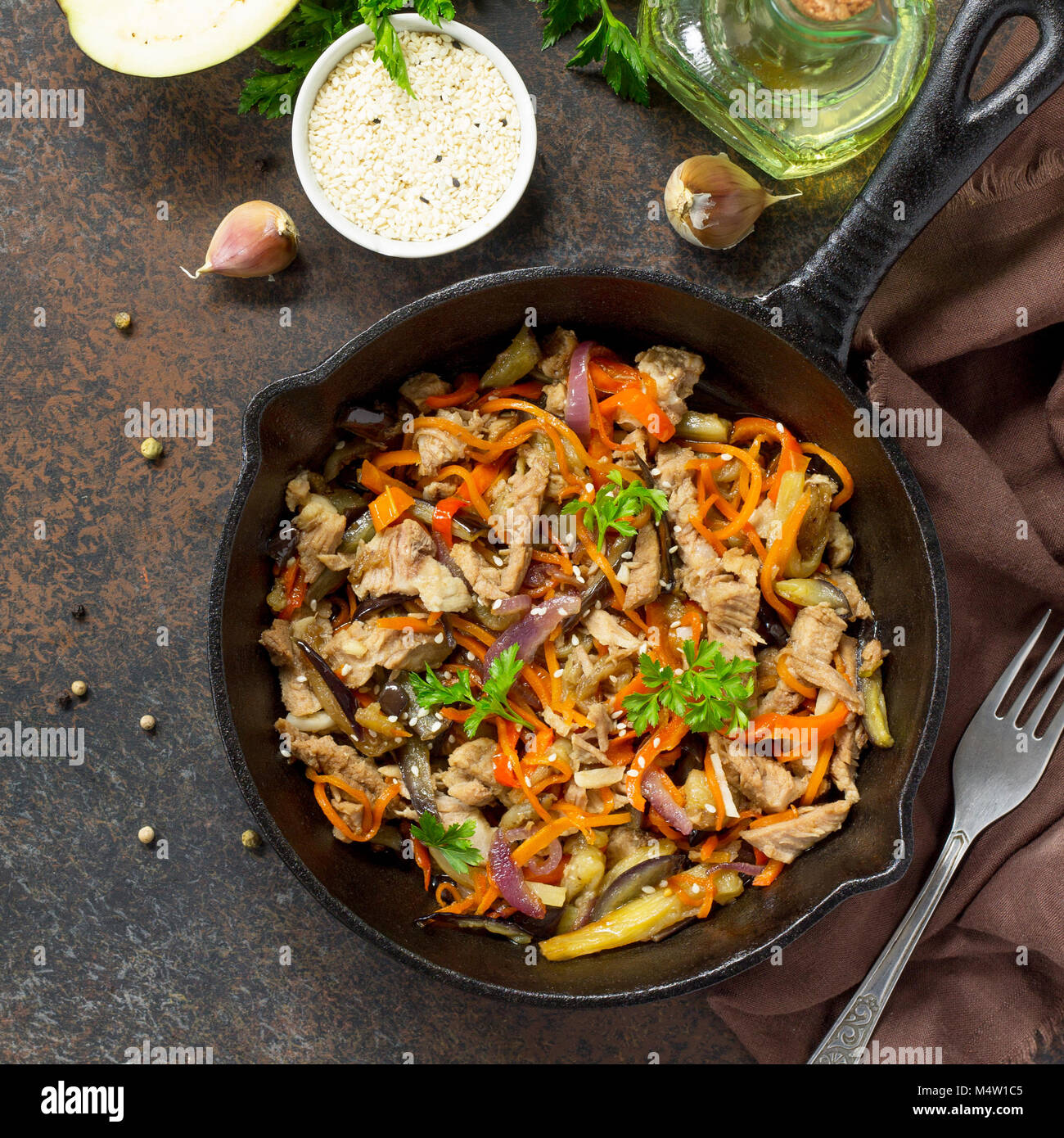 Warm salad with boiled meats and grilled vegetables (eggplant, carrots, paprika) on dark stone or slate background. - Stock Image