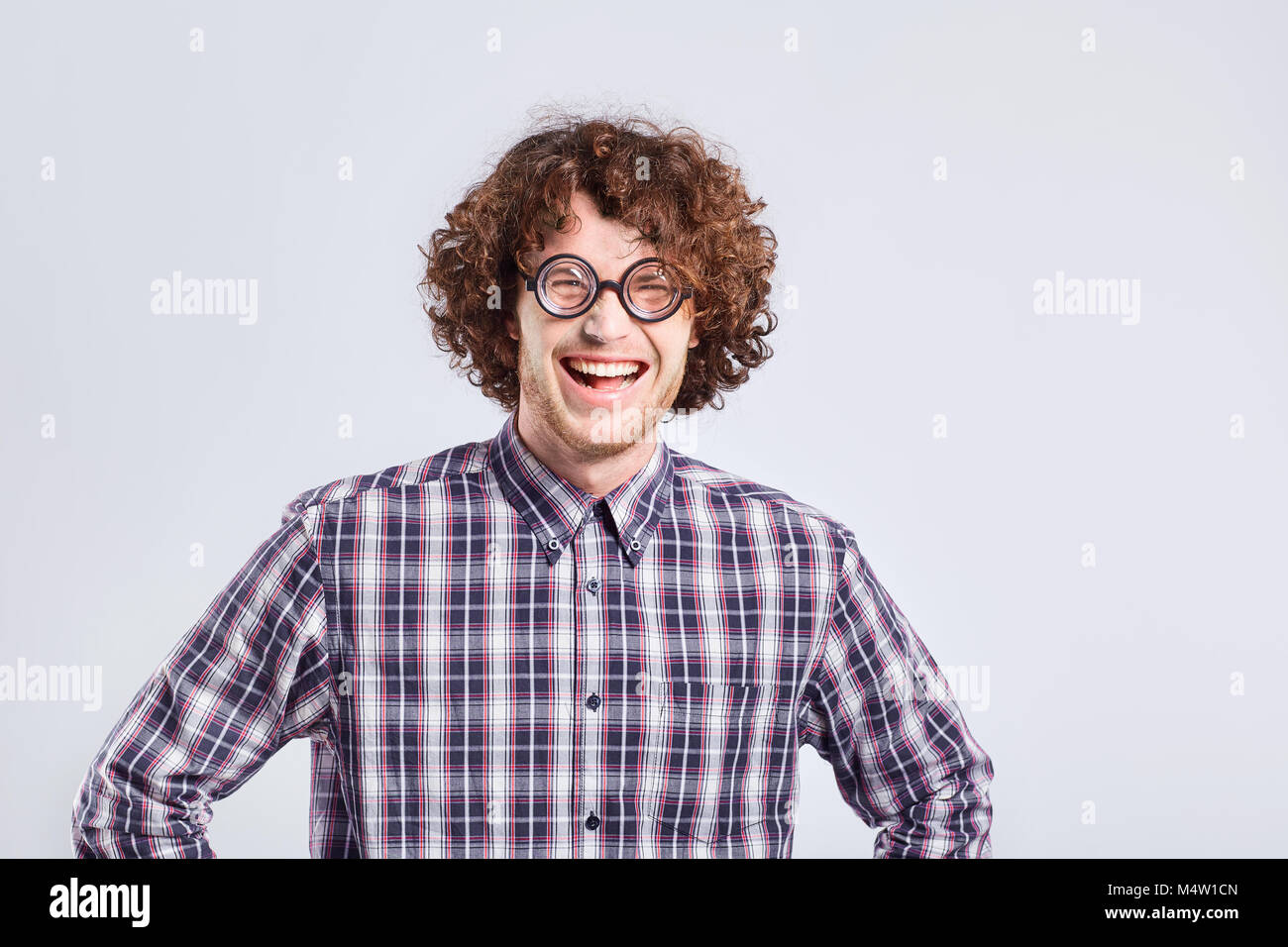 Curly nerd man in glasses with a stupid kind of funny emotion. - Stock Image
