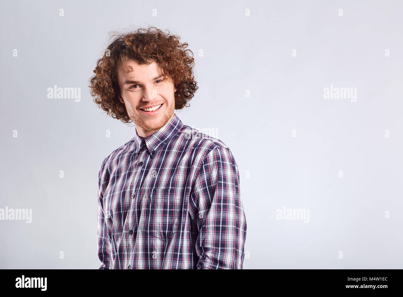 Curly guy smiles with a positive emotion. - Stock Image