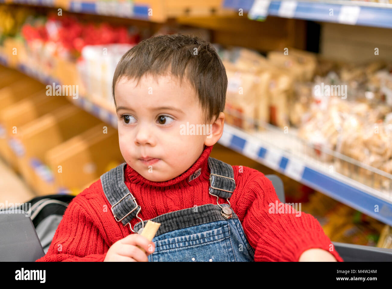Boy 2 years in a store on the background of bread. - Stock Image