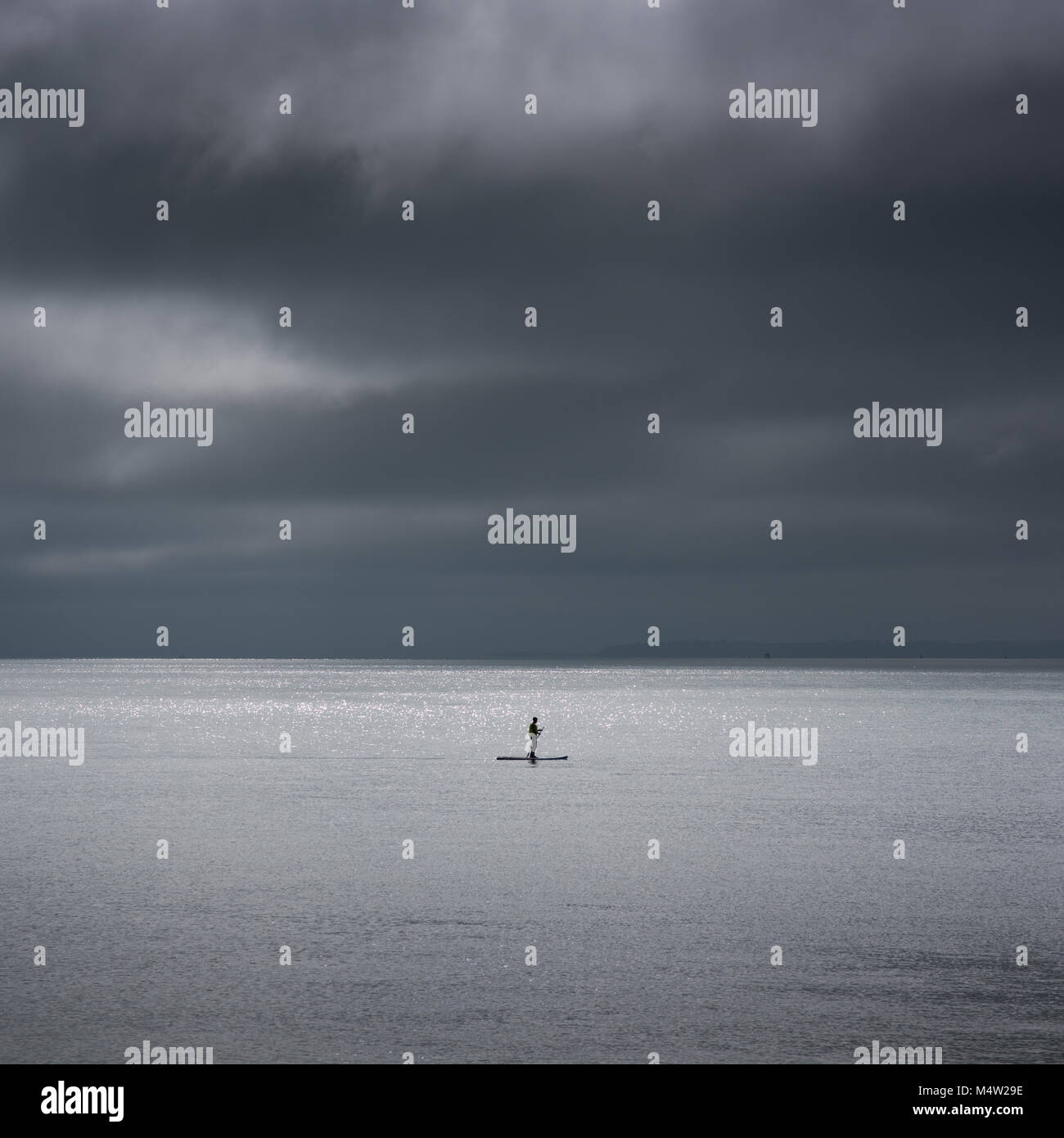 person or silhouette of person paddle boarding in the sea Stock Photo