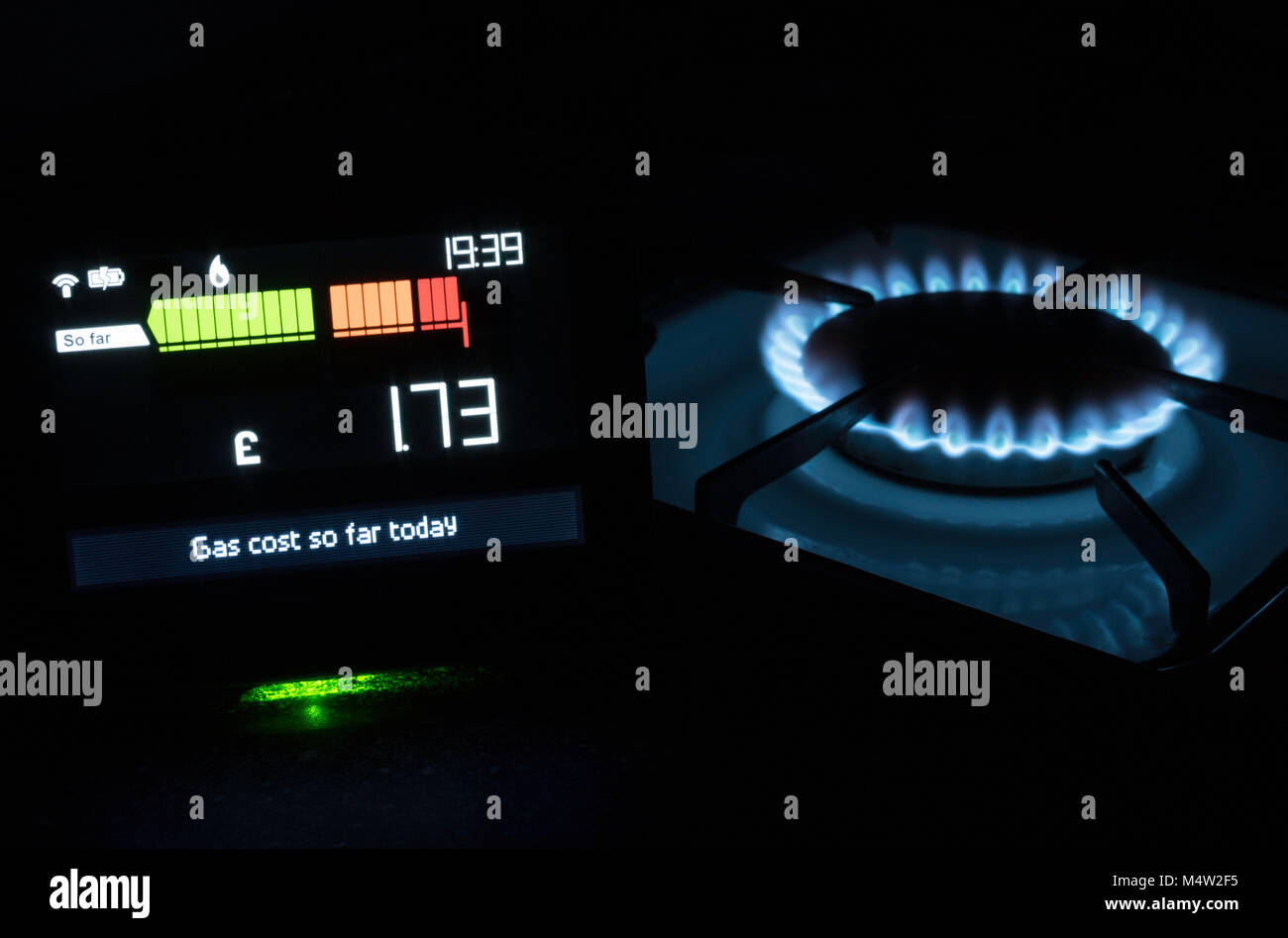 Chameleon Technology Smart meter showing cost of gas used today with gas hob in the background, England, UK - Stock Image