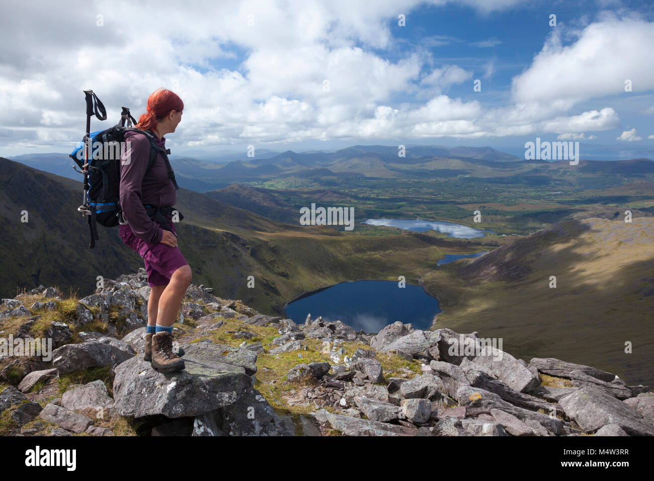 Hiker looking over Coomloughra Lough from Beenkeragh, MacGillycuddy's Reeks, County Kerry, Ireland. - Stock Image