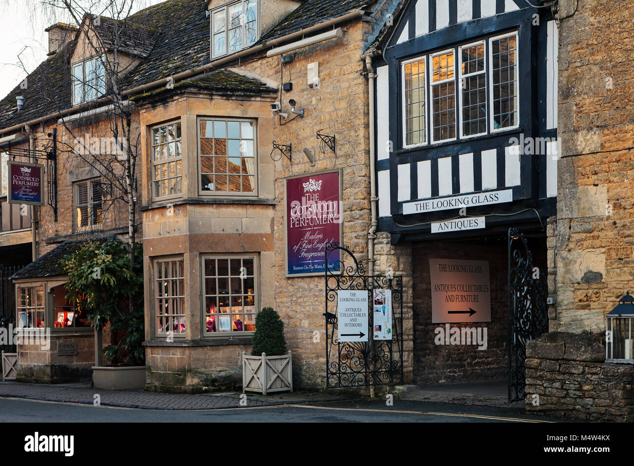 BOURTON ON THE WATER, UK - FEBRUARY 15th, 2018: Row of shops in Bourton-on-the-Water, which  is a village in Gloucestershire - Stock Image