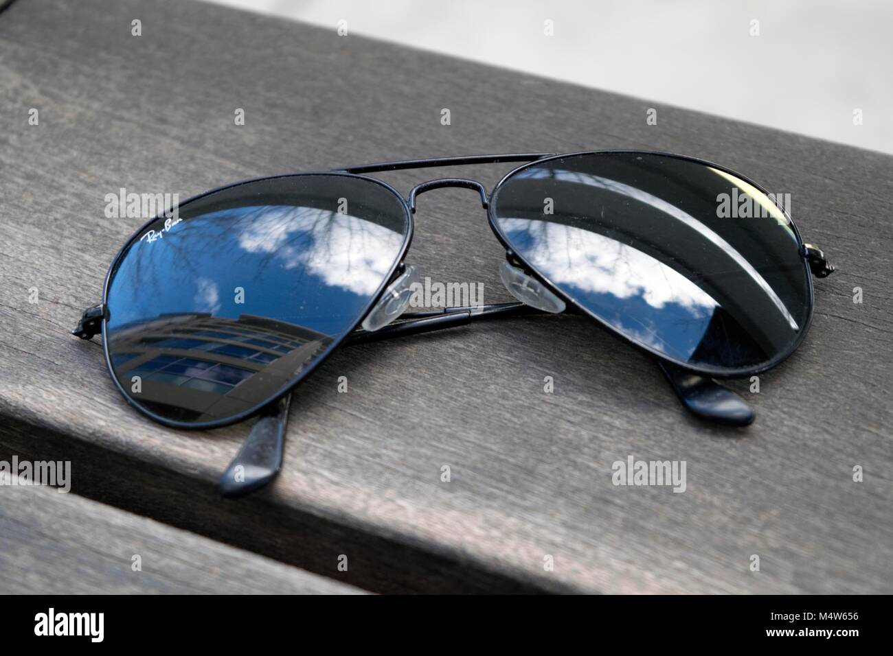 A pair of sunglasses rests on a table at a cafe. Stock Photo