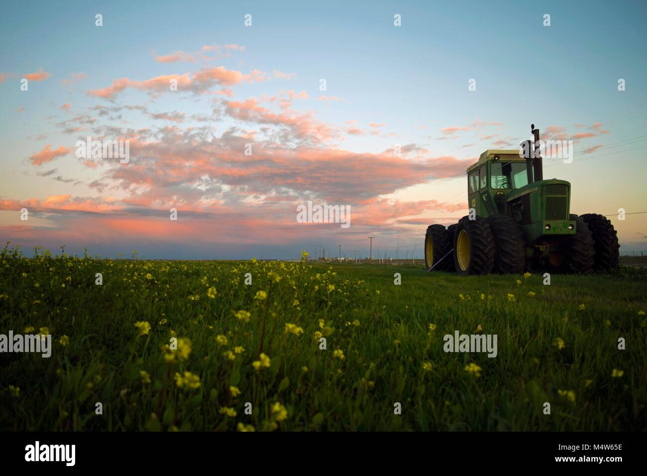 A tractor sits unused in a field during sunset outside of Woodland, CA. Stock Photo