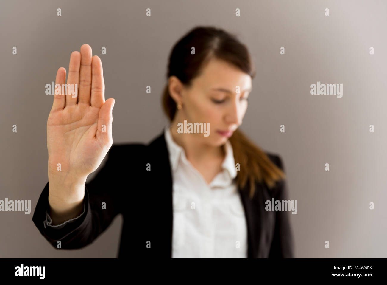 Woman in business suit showing her palm, body language, say NO at work, self-awareness - Stock Image
