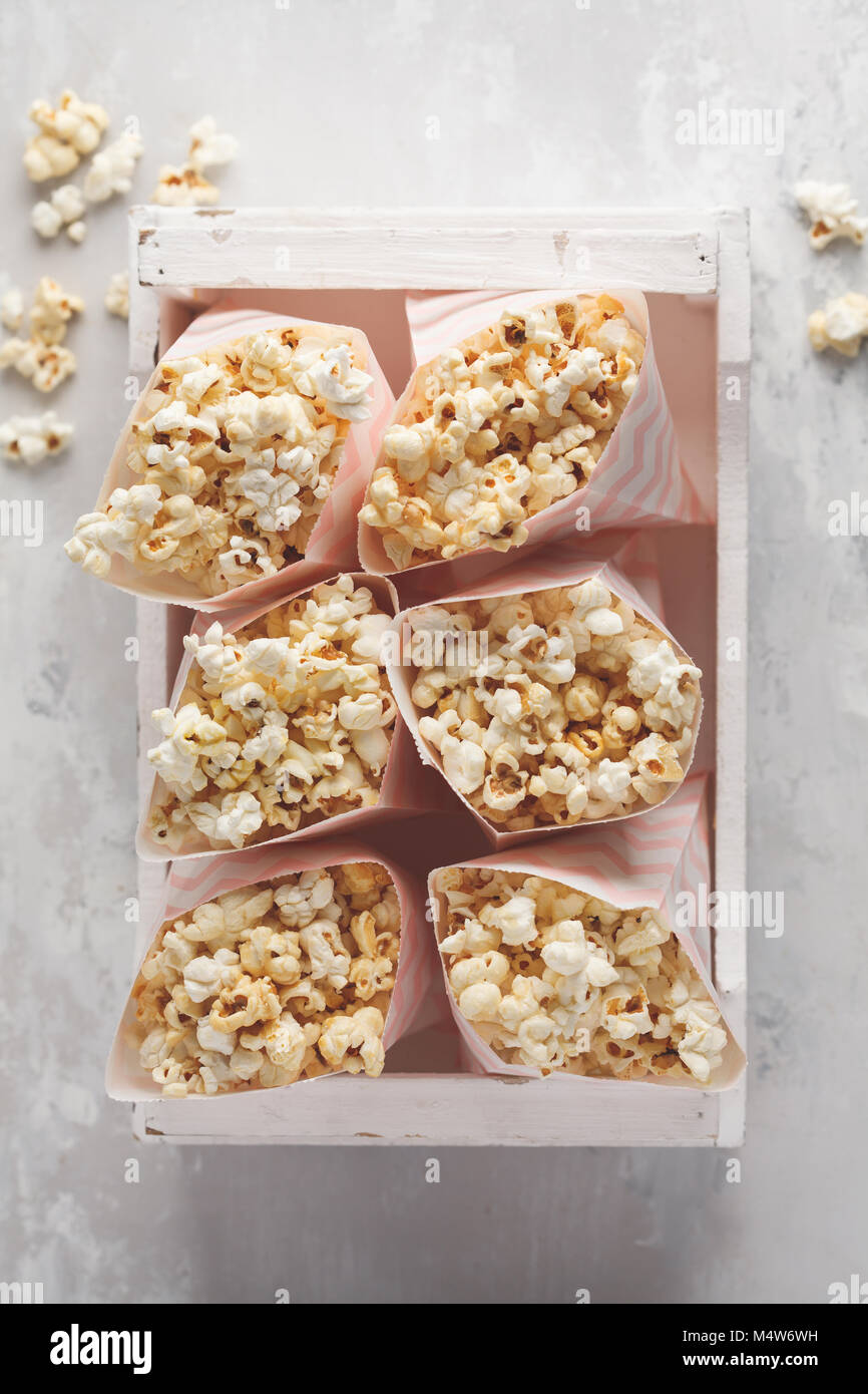 Golden caramel pop corn in paper bags in a white wooden box. - Stock Image