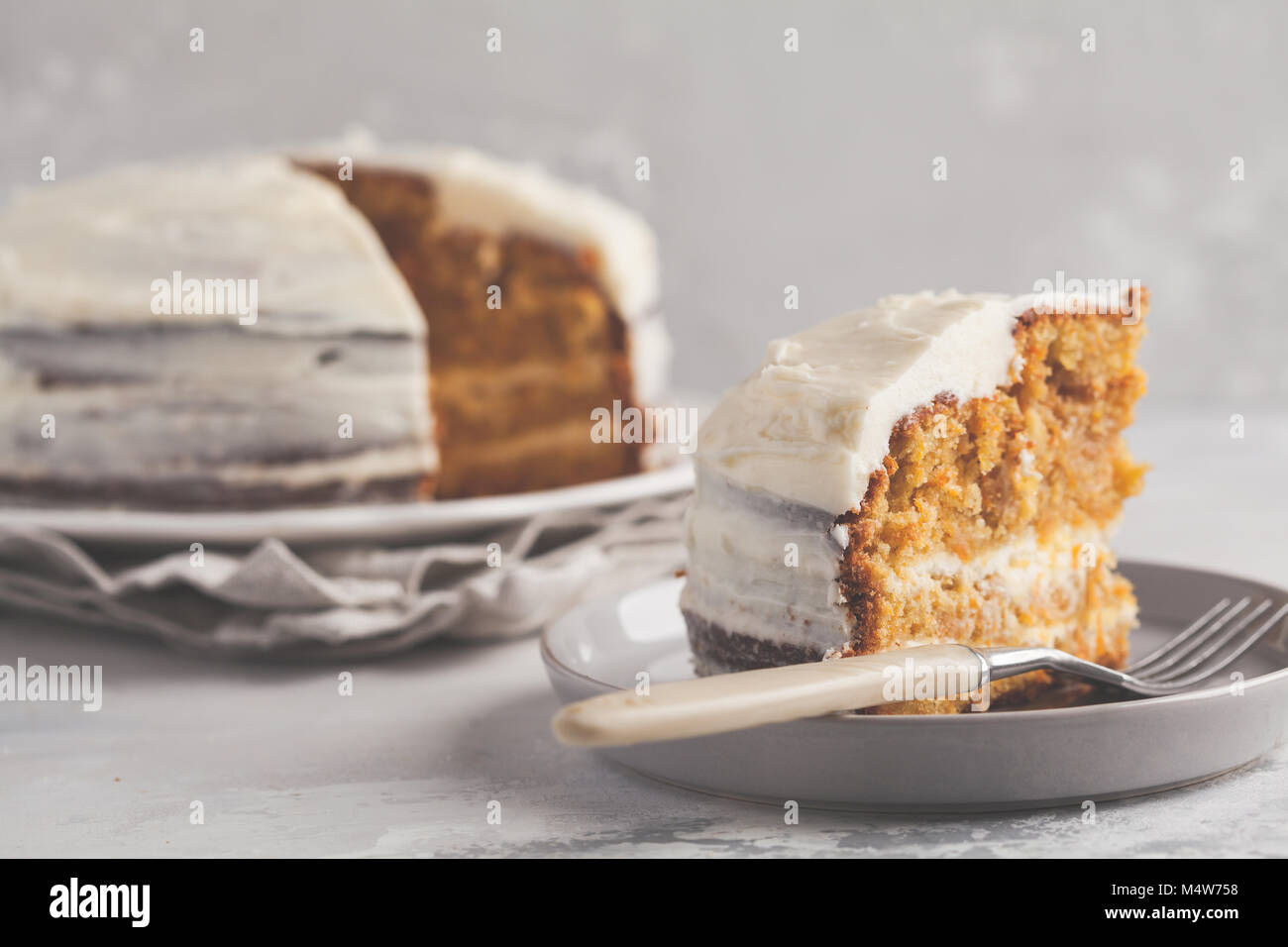 Carrot homemade cake with white cream on a gray background. Festive dessert concept. - Stock Image