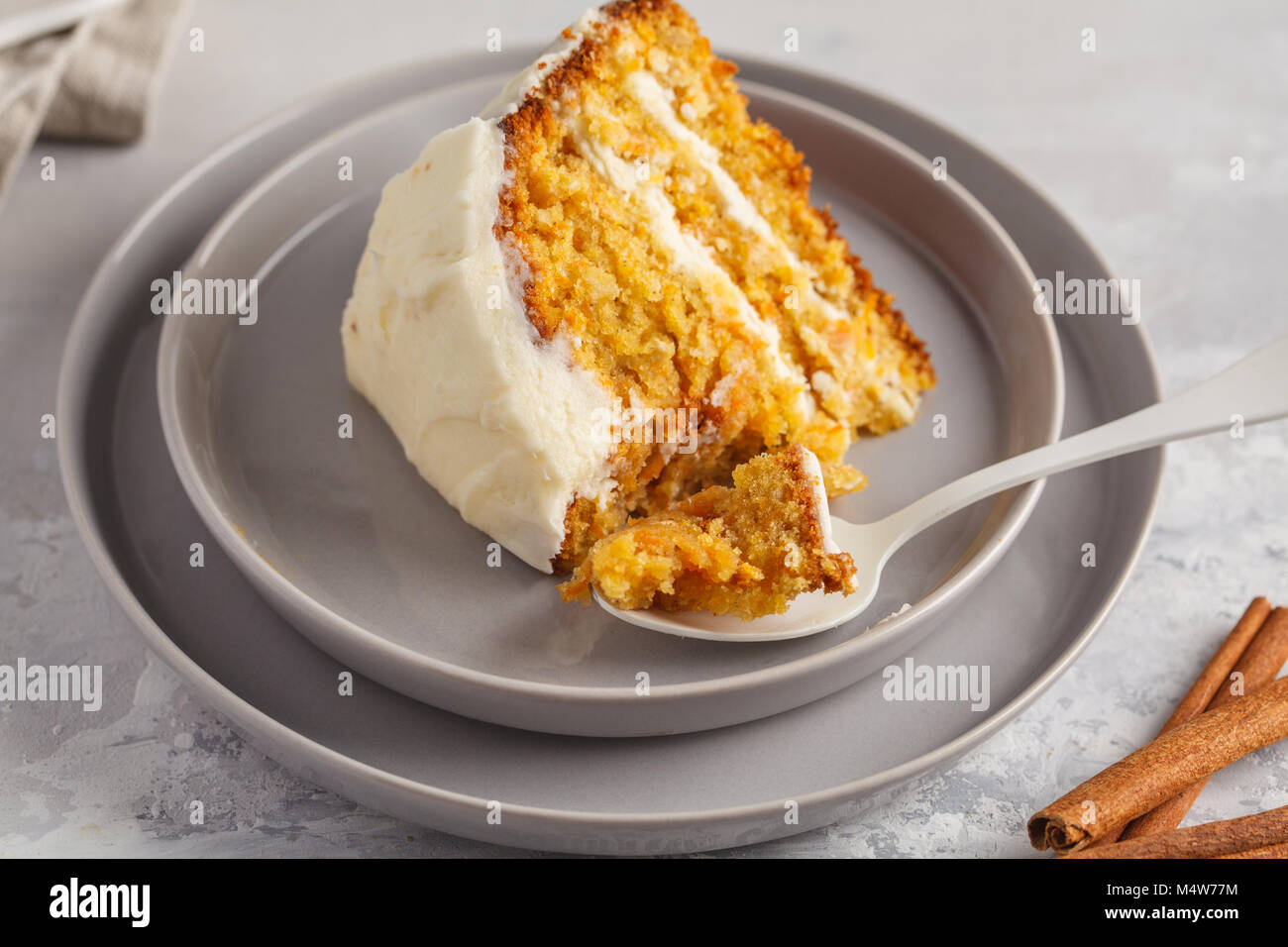 Piece of carrot homemade cake with white cream on a gray background. Festive dessert concept. - Stock Image