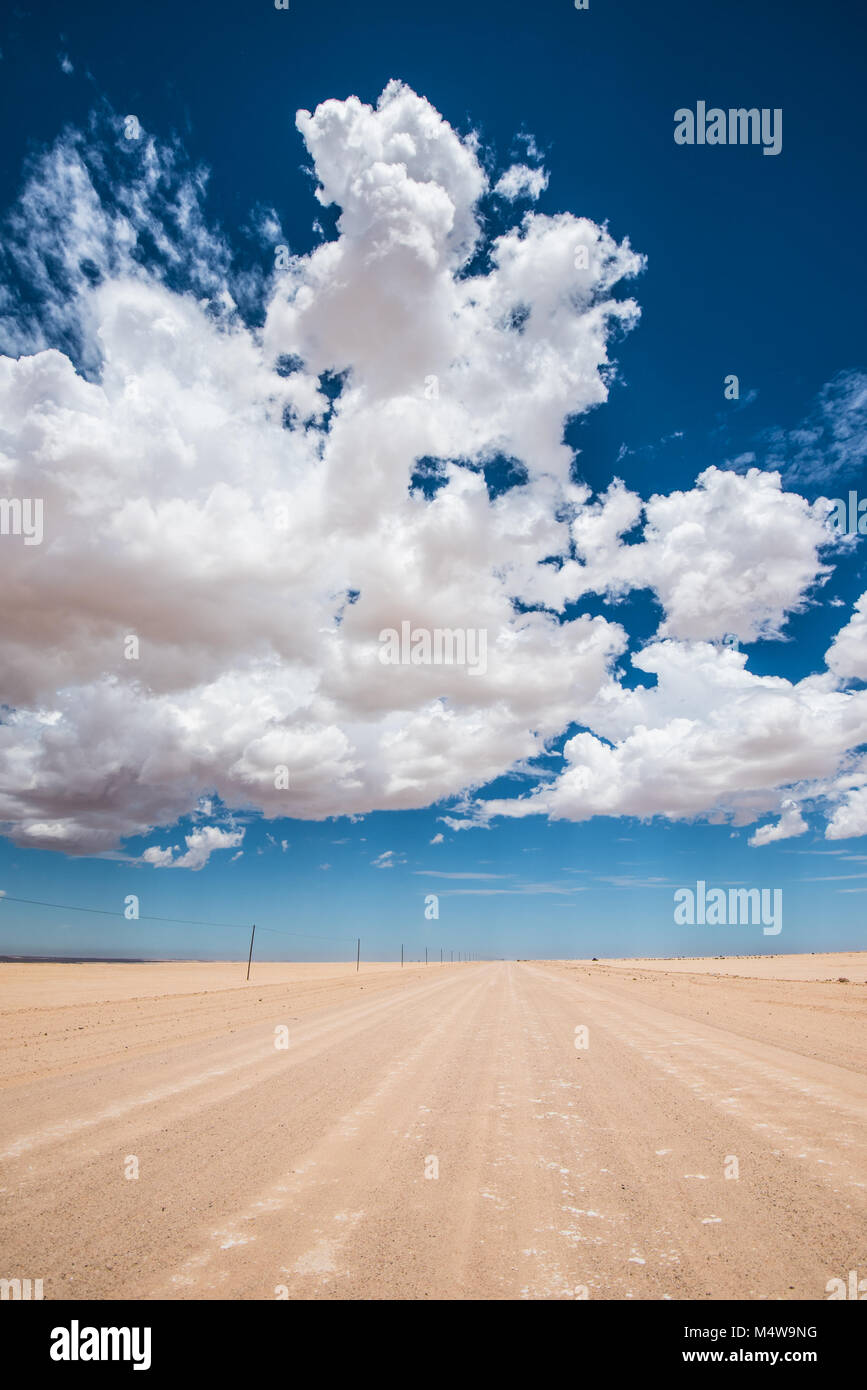vibrant image of desert road and blue cloudy sky - Stock Image