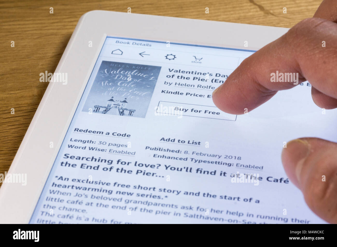 A user buying an Ebook on a kindle paperwhite Ebook reader - Stock Image