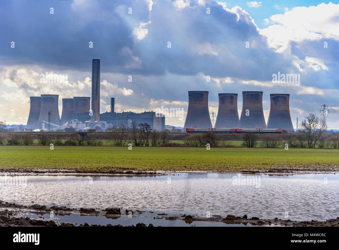 An East Midlands train passes Fiddlers Ferry power station. - Stock Image