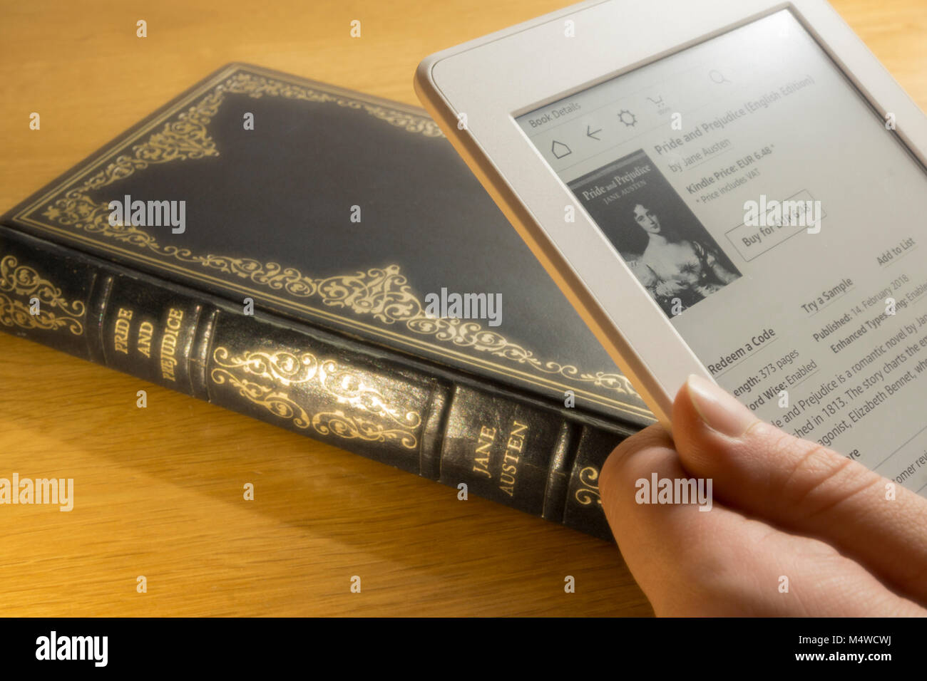A user buying an eBook copy of Pride and Prejudice, with a hardback copy of the book in the background - Stock Image
