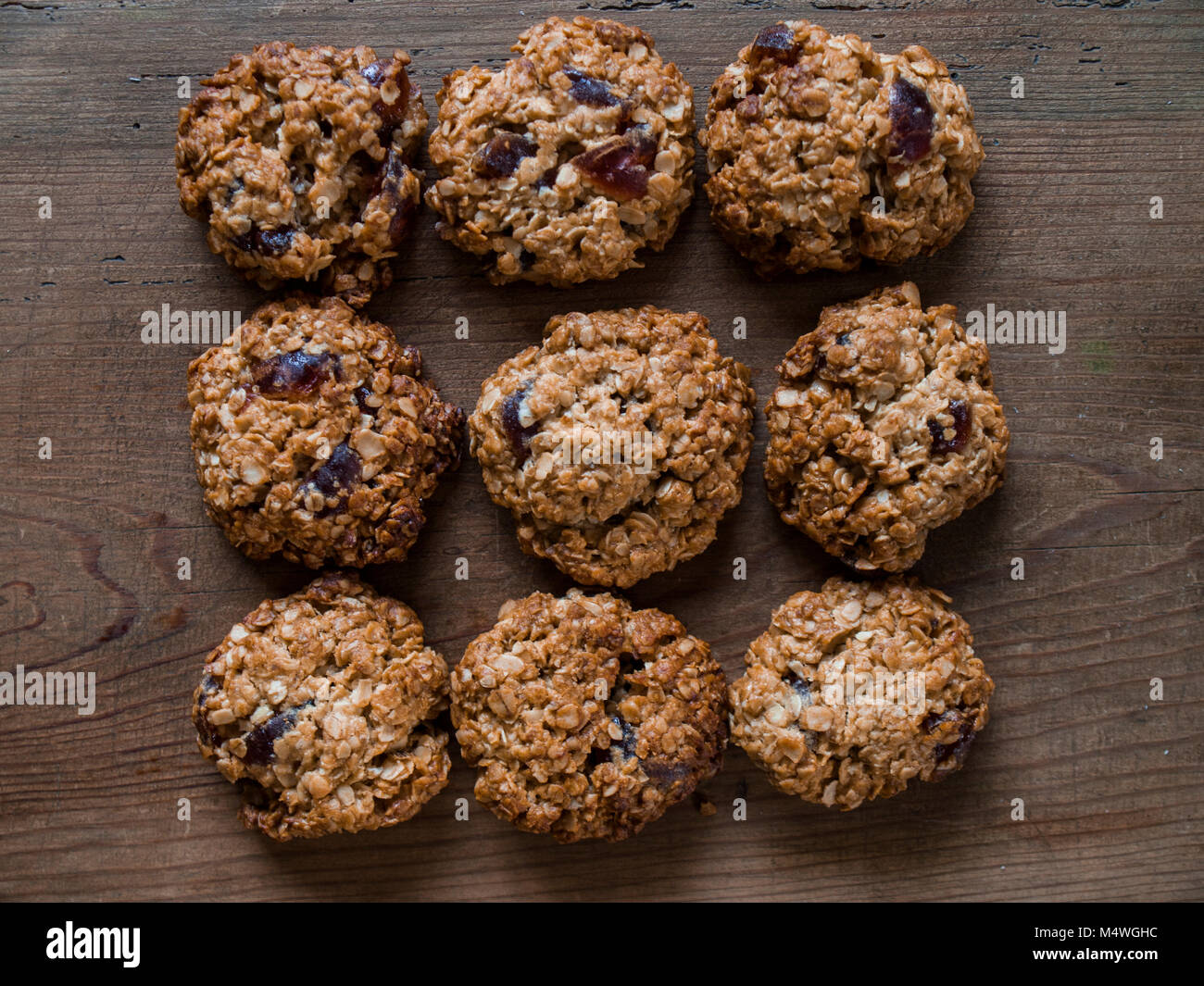home made oat biscuits with dried cherries. View from above with a rustic background. - Stock Image