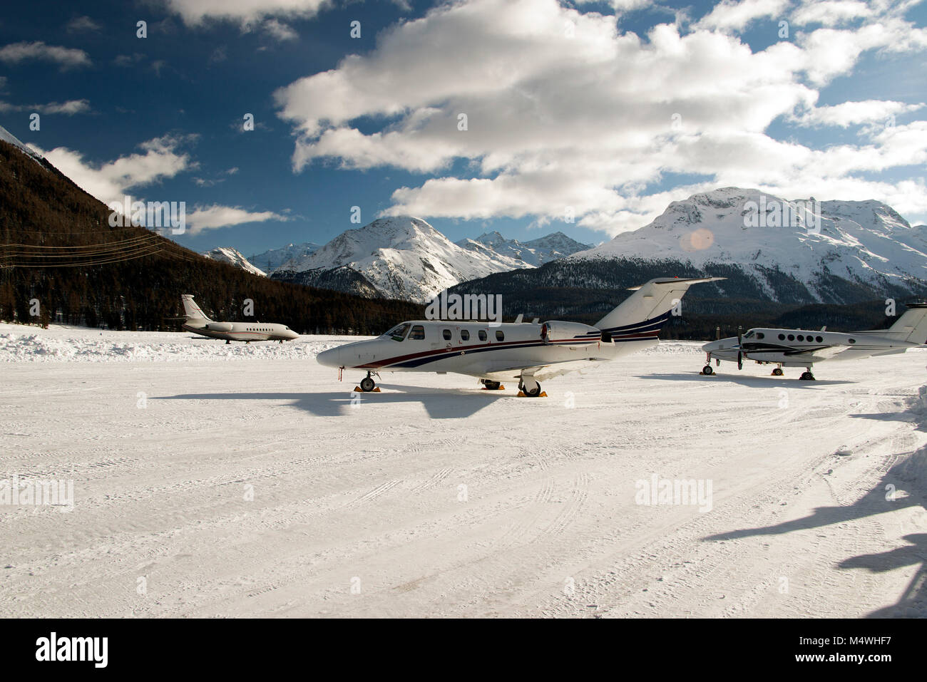 Private jets and a propeller type airplane taking off in the airport of St Moritz Switzerland in winter - Stock Image