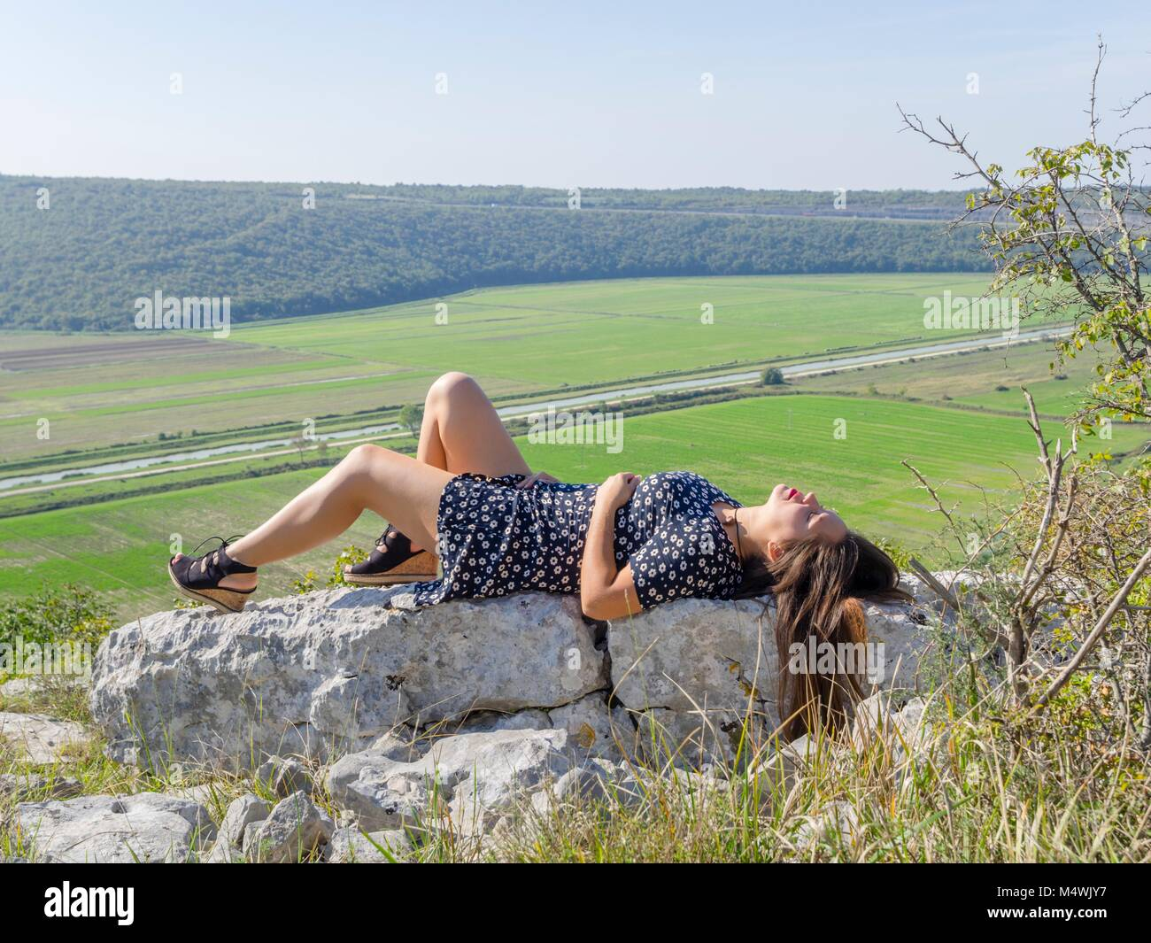 Young woman is enjoying nature naturelover natureaddict lazy afternoon relief lying on back profile sideview at Stock Photo