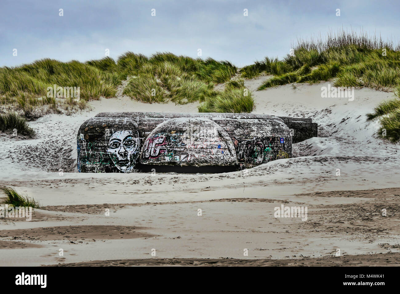 Remains of a WW2 bunker with graffiti at a French beach - Stock Image