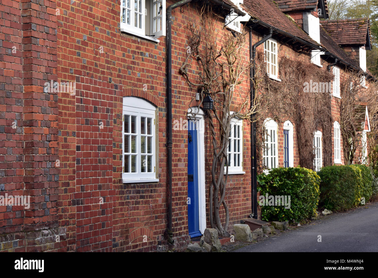 An attractive or chocolate box picturesque typically English row of country cottages in a Hampshire village. Terraced - Stock Image