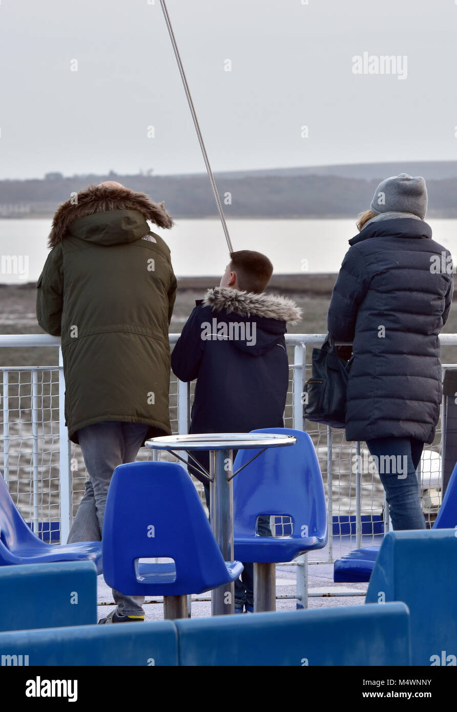 A family of three two adults and a child standing on the upper deck or outside deck of the Isle of Wight car ferry - Stock Image