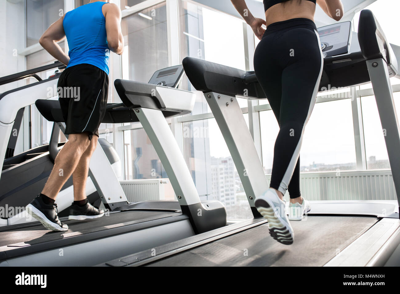 Mid-section back view of two fit young people, man and woman, running on treadmills facing windows in modern gym, - Stock Image