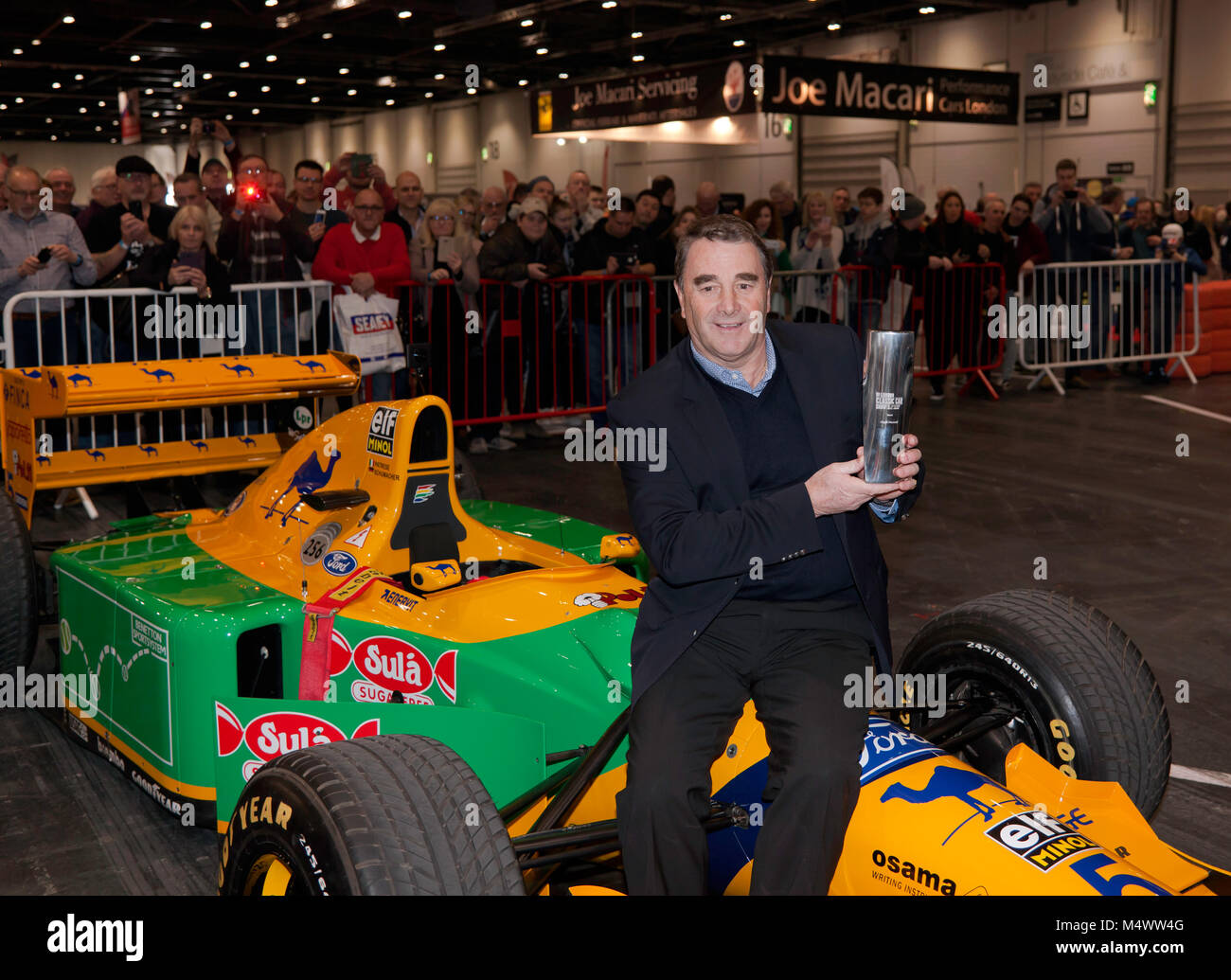 "Nigel Mansell CBE posing  with the London Classic Car Show ""Icon"" award,  in the Grand Avenue, after his drive in Stock Photo"