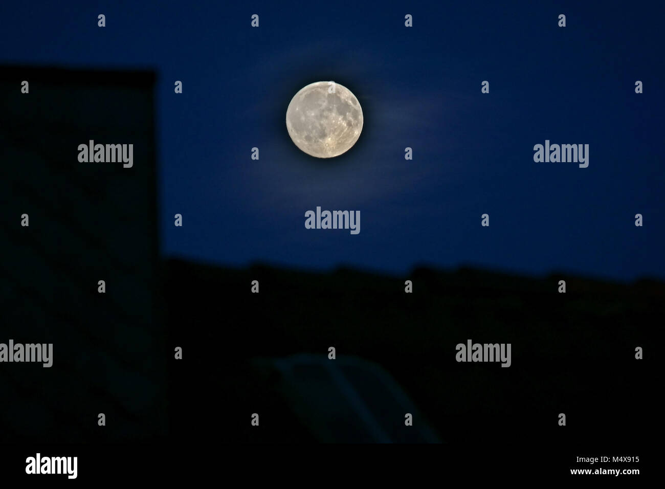 Grey full moon in dark sky above black house roofs - Stock Image