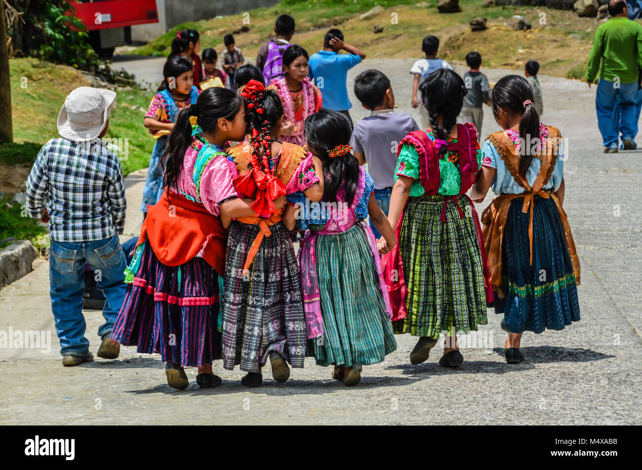 Group of Guatemalan school children walk on road, holding hands, when one little girl whispers in a friend's - Stock Image