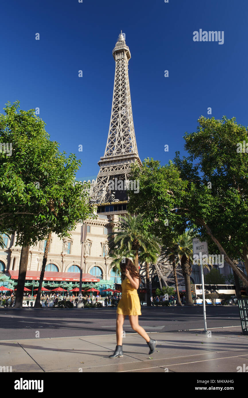 Young woman walking on the sidewalk, Paris Hotel in the background, Las Vegas, Nevada. - Stock Image