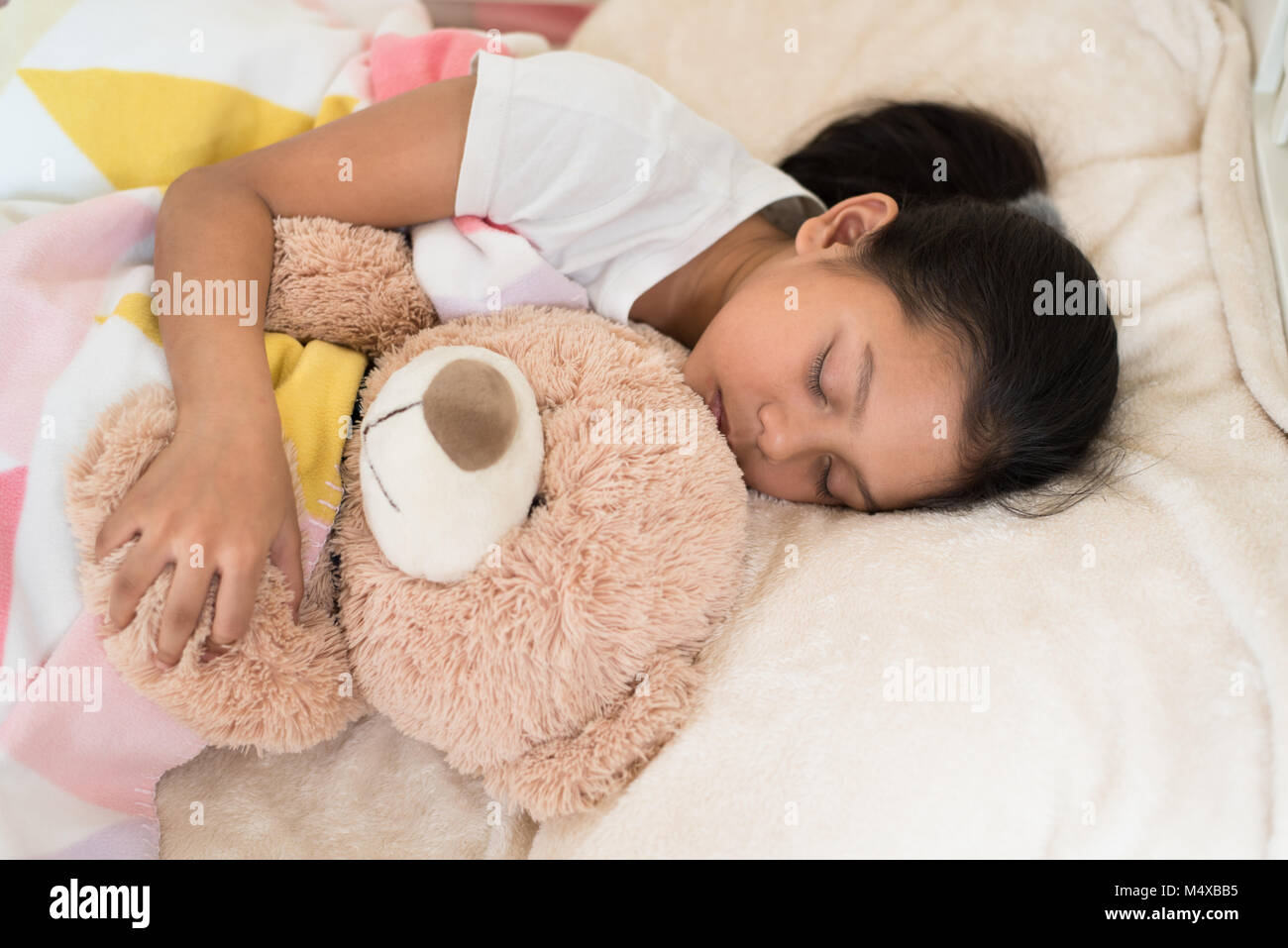 young little asian girl sleeping while hugging teddy bear. sleep concept - Stock Image