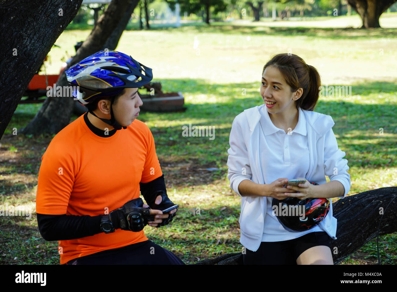 Man is socialising by having a chat with female cyclist in a park. - Stock Image