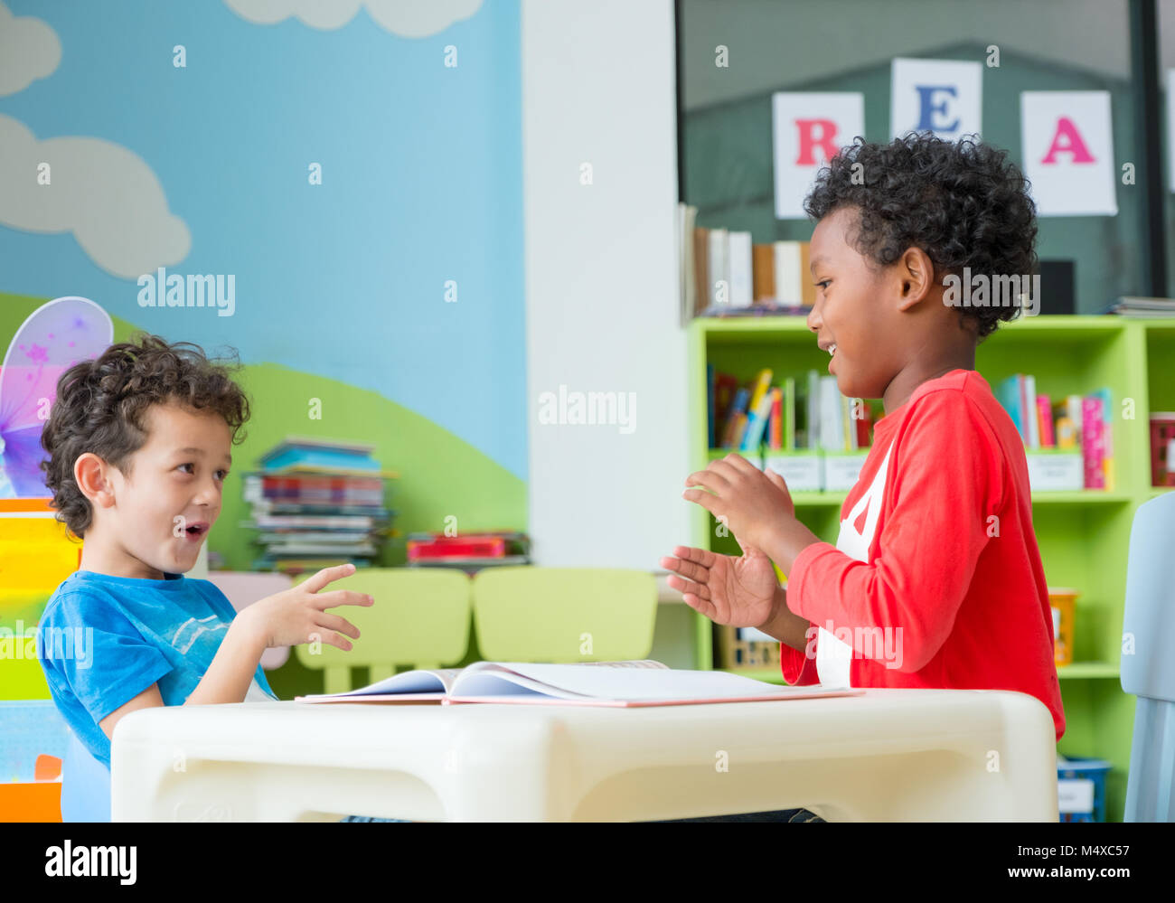 Two Boy Kid Sit On Table And Coloring In Book Preschool LibraryKindergarten School Education Concept