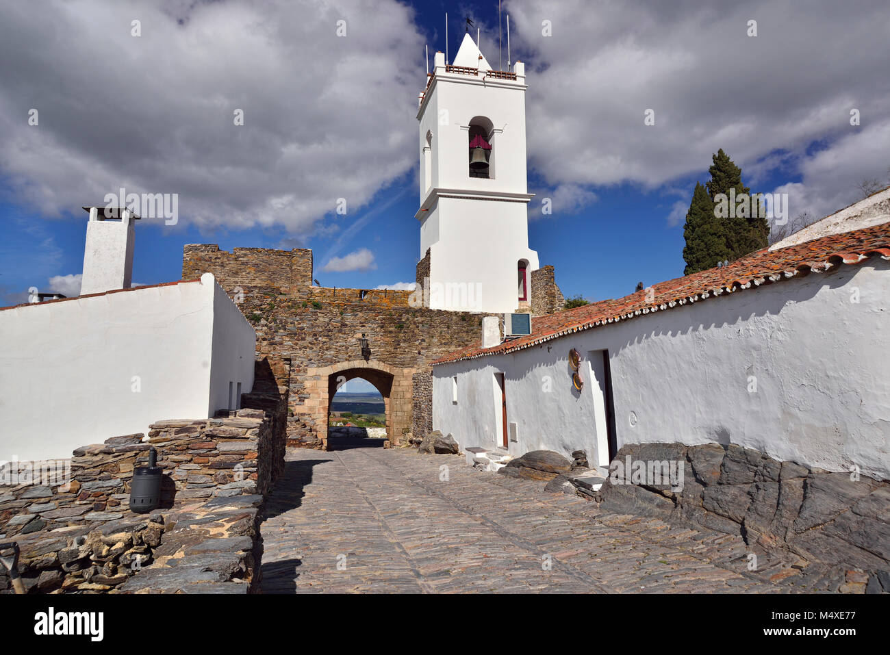 Medieval stone paved alley with white washed houses and bell tower - Stock Image