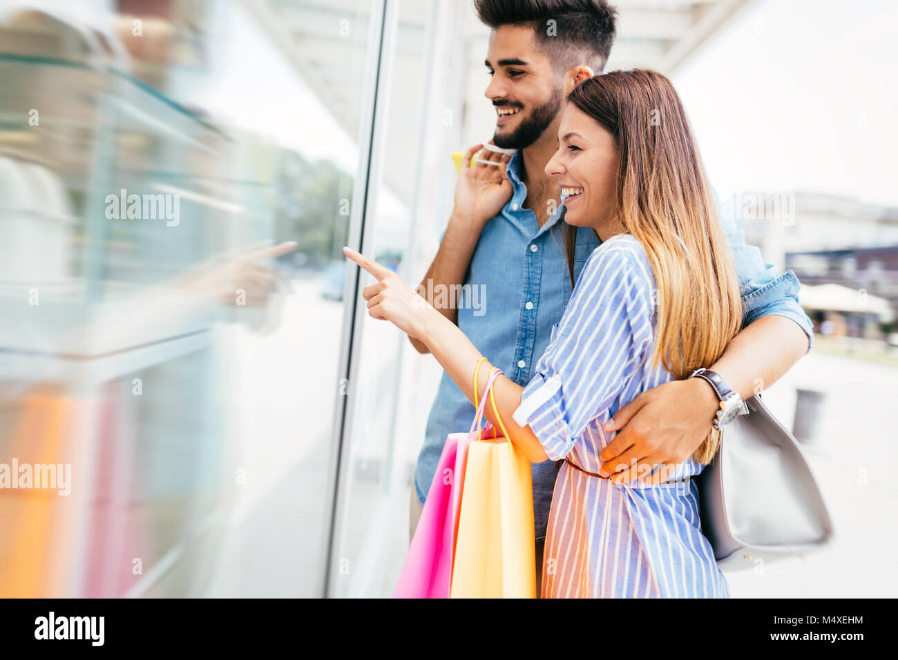 Happy attractive loving couple enjoy shopping together - Stock Image