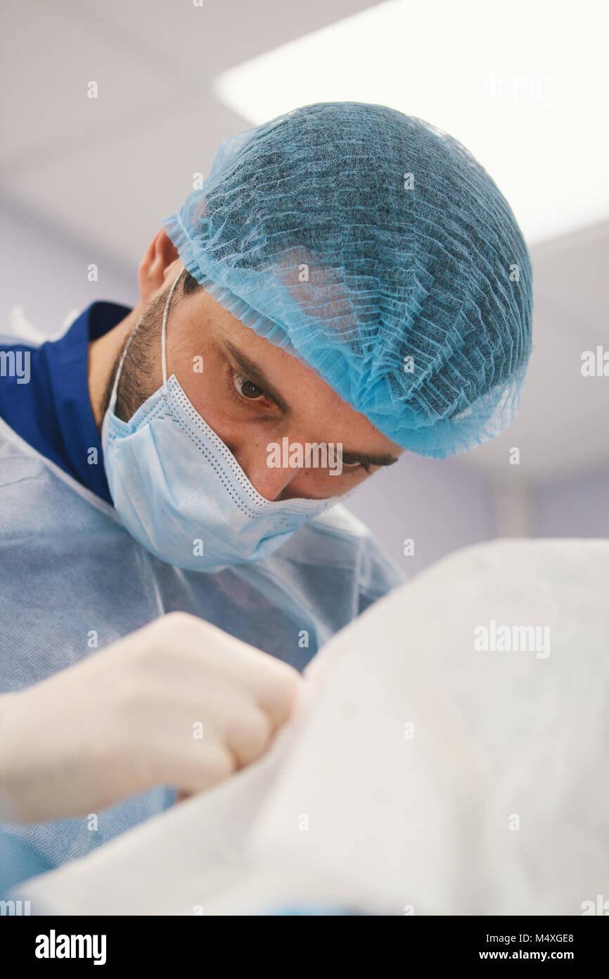 Doctor surgeon looking at a patient in operating theater - Stock Image