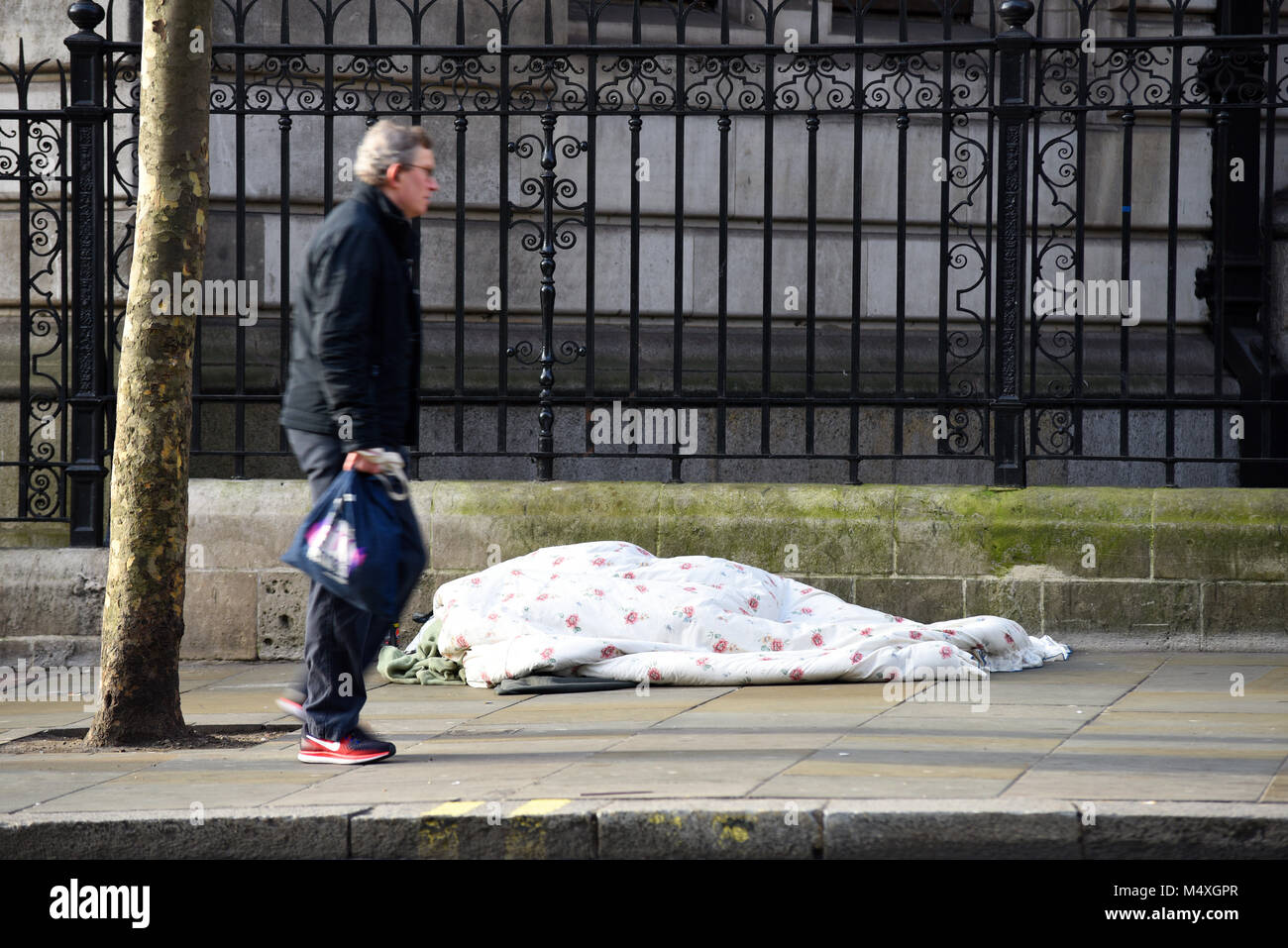 Walking by homeless person sleeping on the street in London. Homelessness. Passer by ignoring rough sleeper on cold - Stock Image