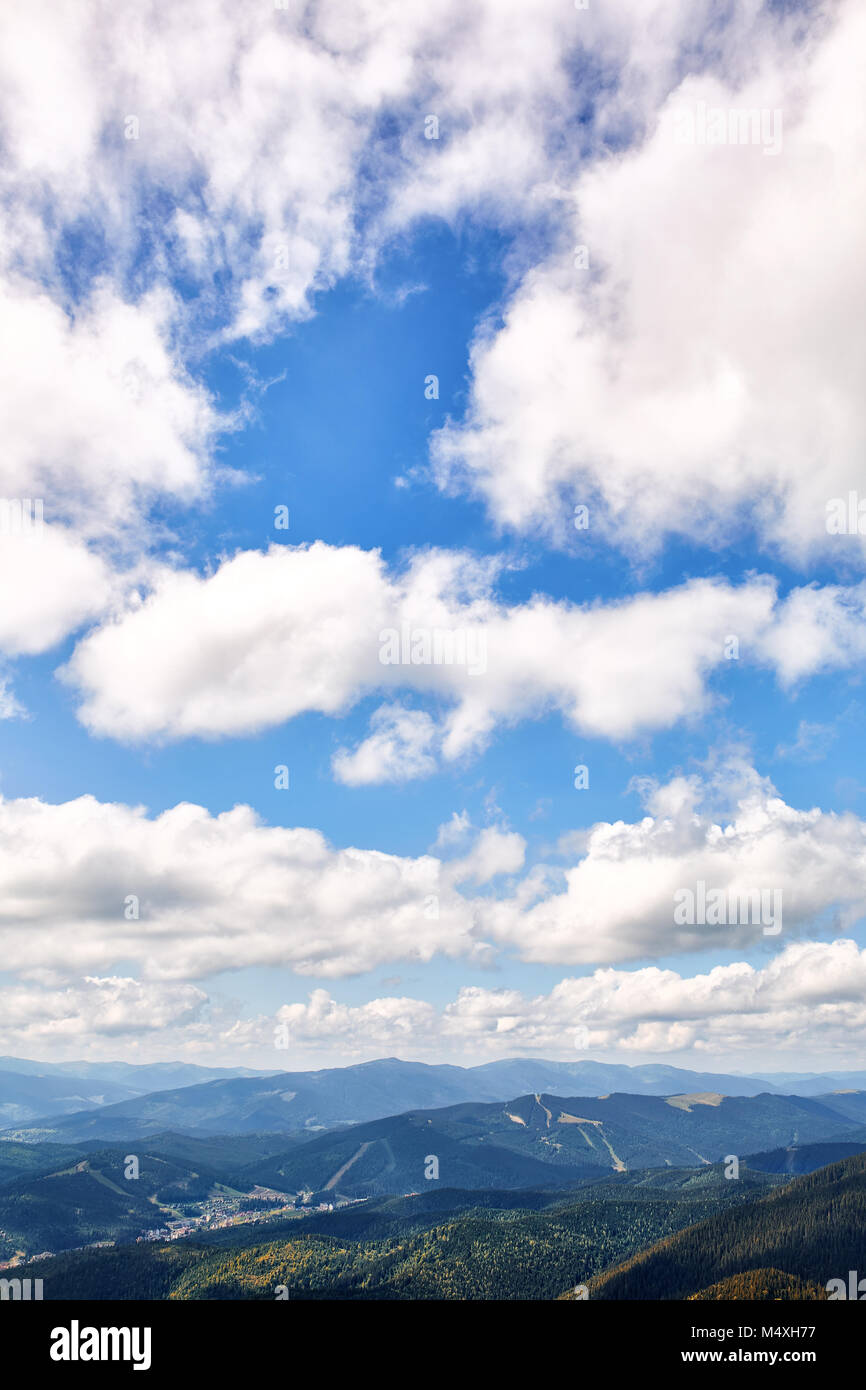 Vertical Picture Of A Bright Blue Sky And Foggy Mountain Background With  White Fluffy Clouds