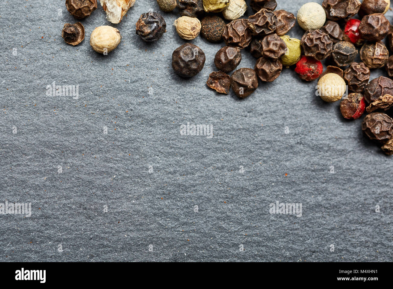 mixture of pepper peas powder scattered on a slate plate. Closeup Stock Photo