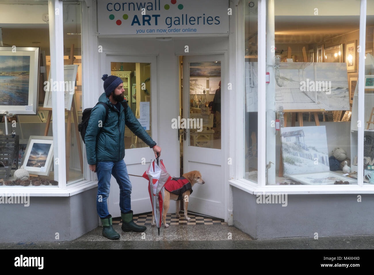 A man and his dog sheltering from the rain. - Stock Image