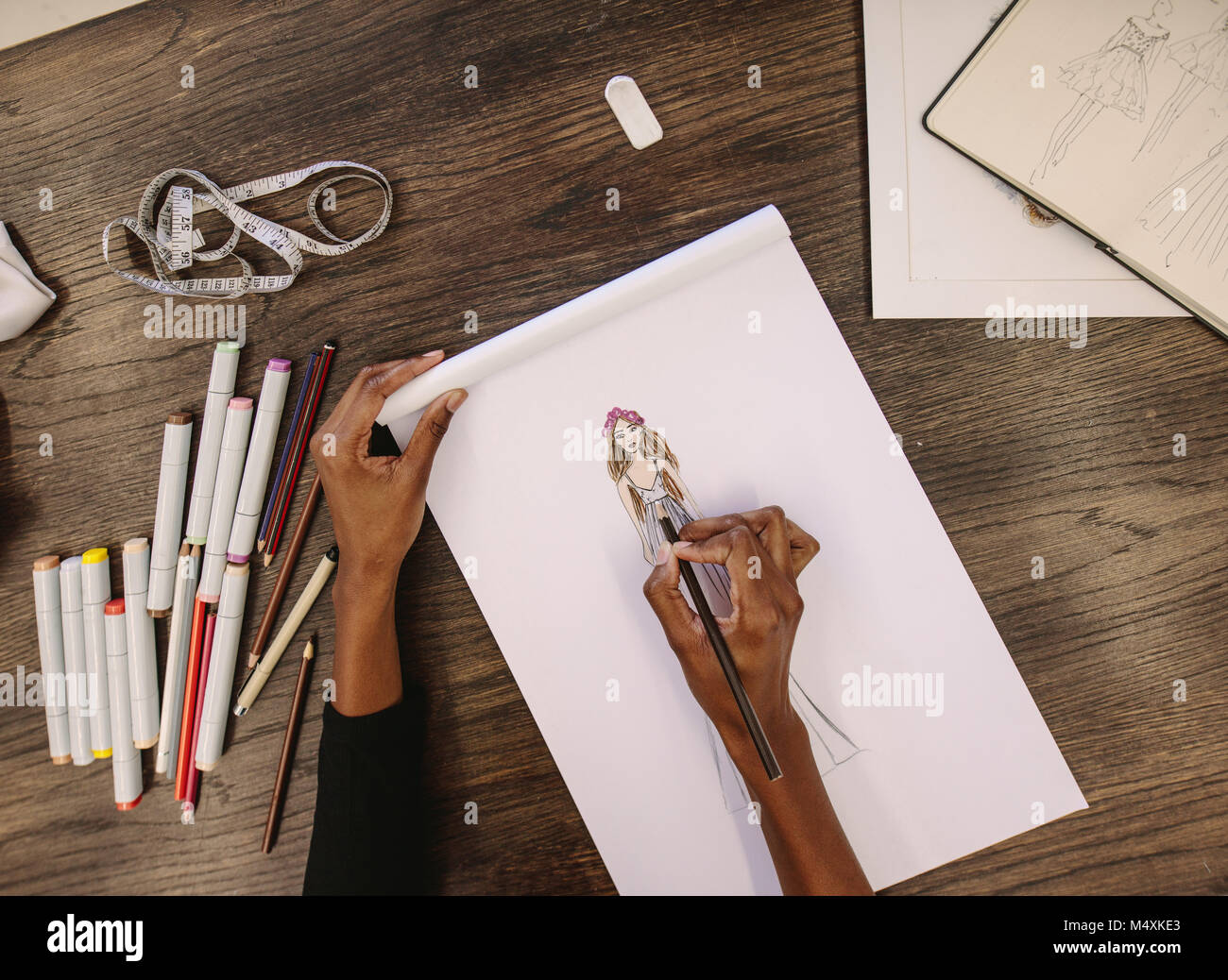 Top view of fashion designer sketching a design sitting at her table. Cropped shot of woman entrepreneur working - Stock Image