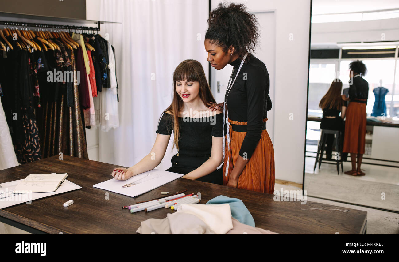 Fashion Designer Sketching A Design Sitting At Her Table While Stock Photo Alamy