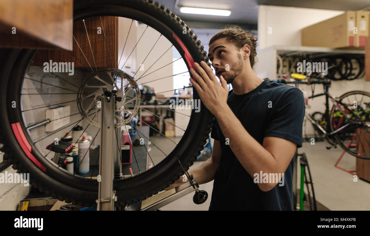 Man working on a bicycle wheel in a repair shop. Worker fixing a bicycle in workshop. - Stock Image