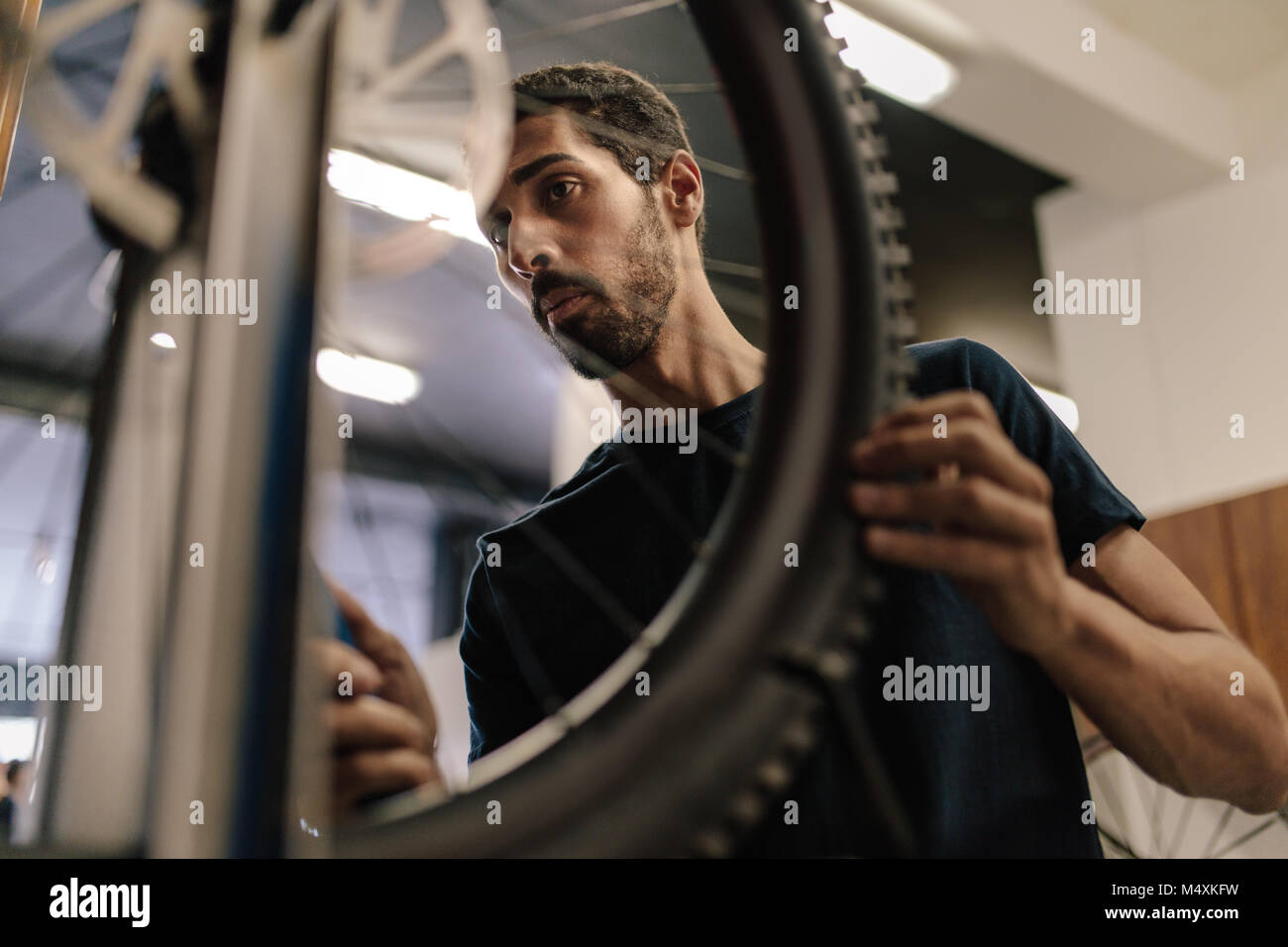 Worker aligning a bicycle wheel in workshop. Man working on a bicycle in a repair shop. - Stock Image