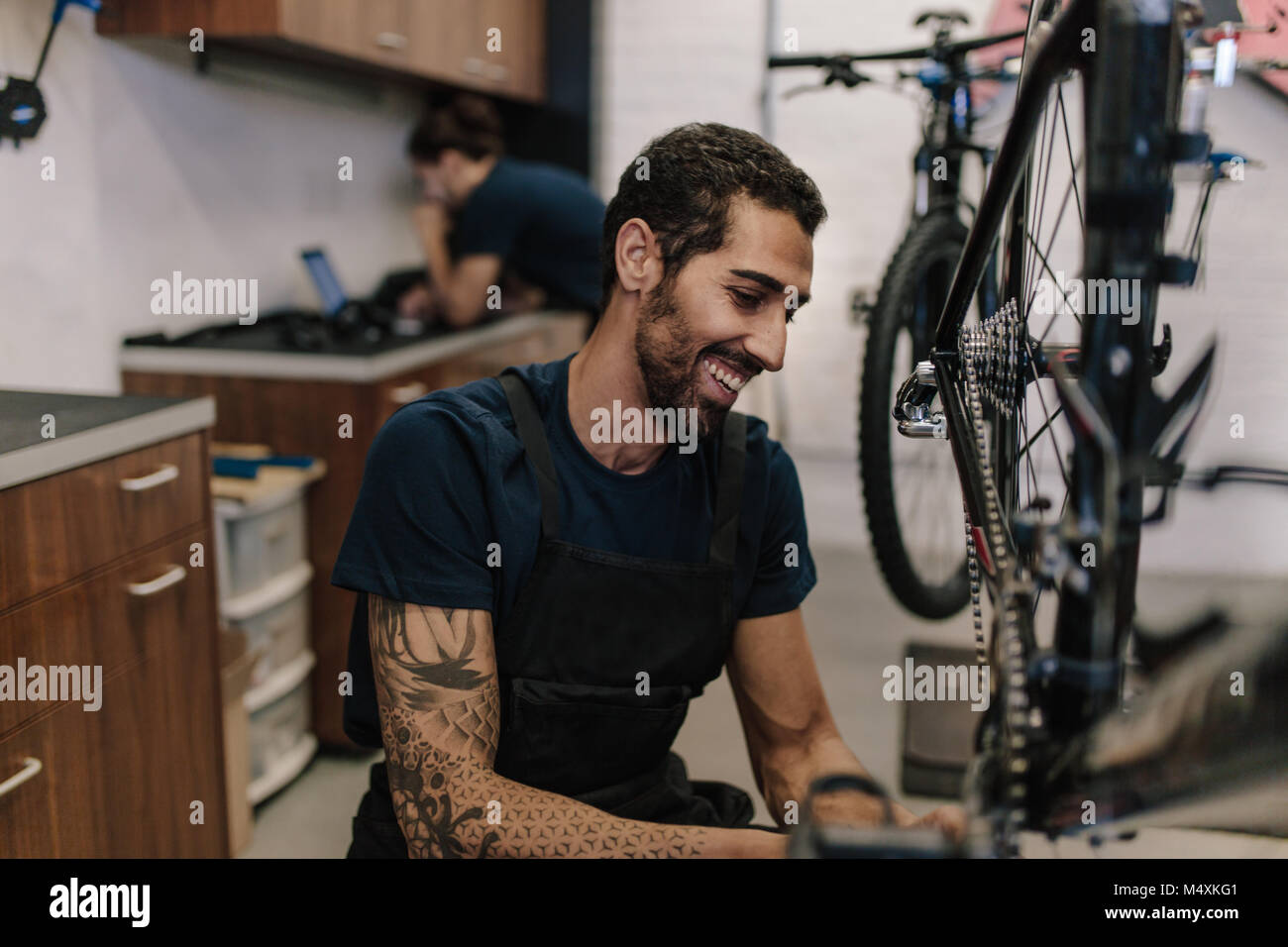Man working on a bicycle in a repair shop. Smiling worker fixing a bicycle in workshop. - Stock Image